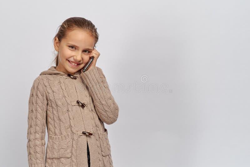 Den lilla unga damen i en varm brun tröja som ser kameran och innehavet, ringer, barnet meddelar i ett angenämt arkivfoto