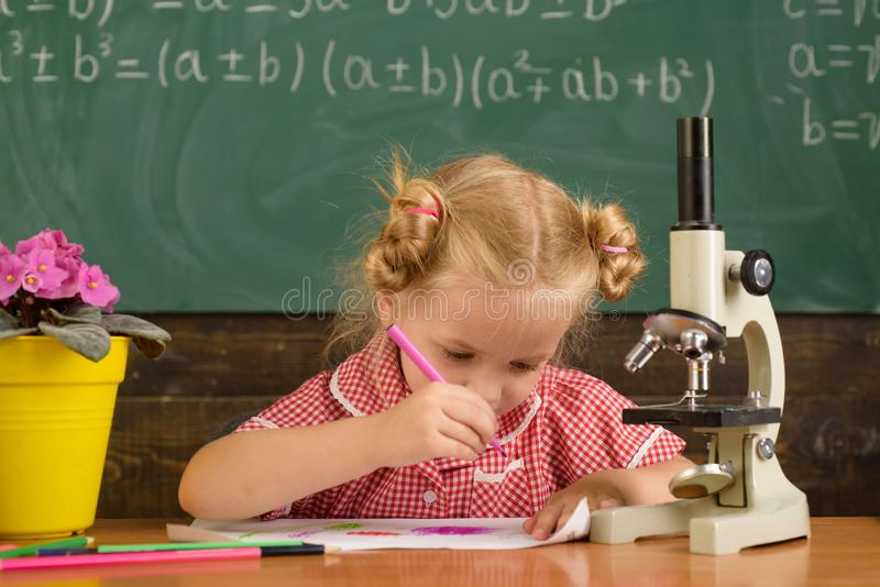Den lilla ungen har kurs Liten ungeattraktion på papper på skrivbordet i daghem arkivbild