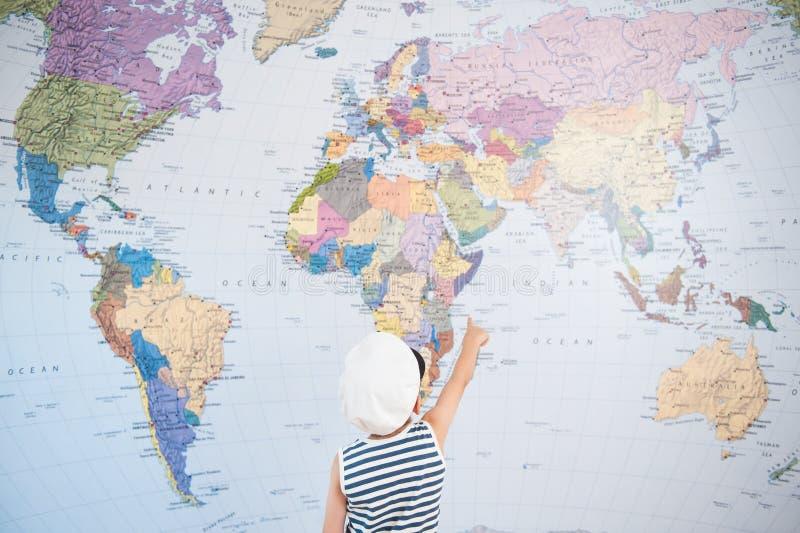 Den lilla ungen i kaptenlock som pekar på världskartan med fingerriktning, turnerar royaltyfri fotografi