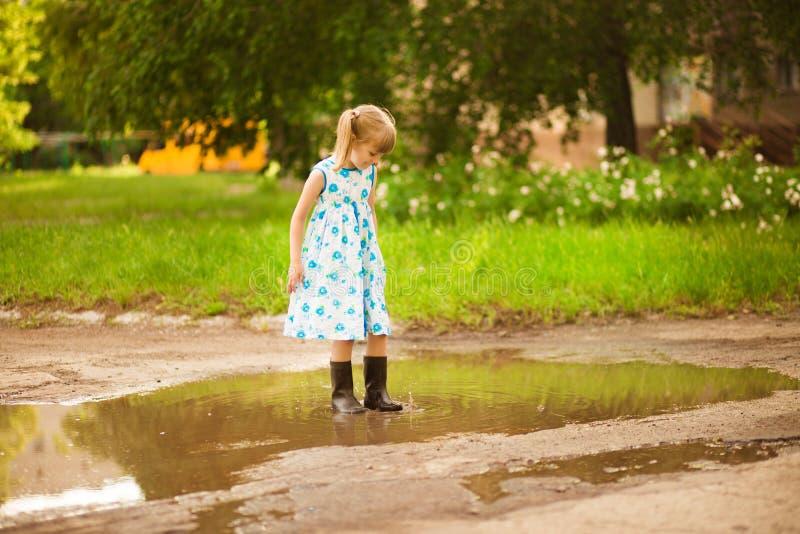 Den lilla ungen kör till och med en pöl Utomhus- sommar royaltyfria bilder
