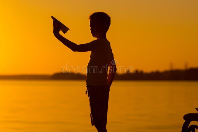 Den lilla ungen rymmer origami av det pappers- flygplanet i hans hand och lekar på solnedgången på bakgrunden av sjön Passionates royaltyfria bilder
