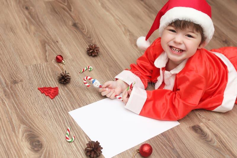 Den lilla ungen skrivar brevet till jultomten arkivbilder