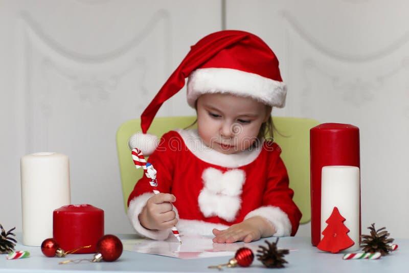Den lilla ungen skrivar brevet till jultomten royaltyfri fotografi