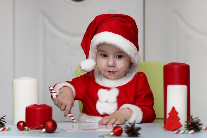 Den lilla ungen skrivar brevet till jultomten arkivfoto