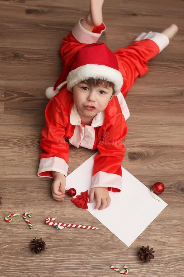 Den lilla ungen skrivar brevet till jultomten arkivbild