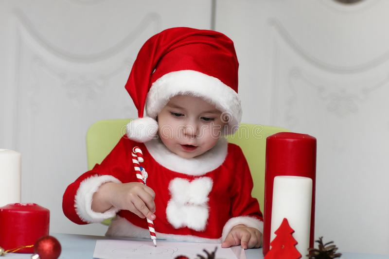Den lilla ungen skrivar brevet till jultomten arkivfoton