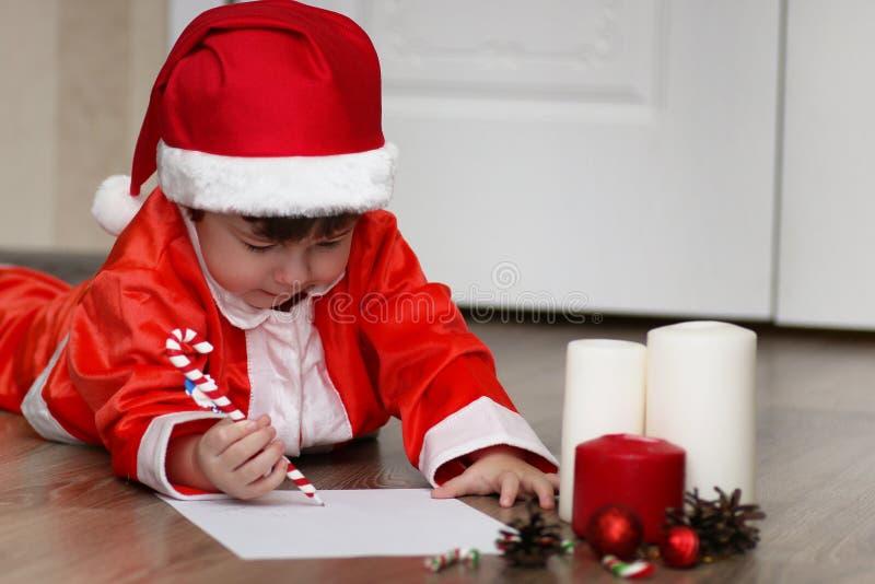 Den lilla ungen skrivar brevet till jultomten royaltyfria foton