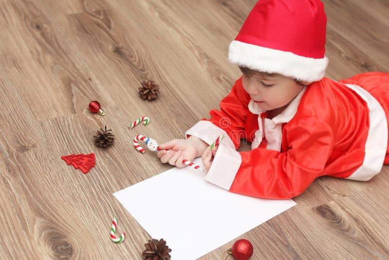 Den lilla ungen skrivar brevet till jultomten royaltyfria bilder