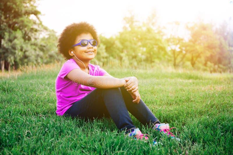 Den lilla ungen som tycker om och lyssnar till musik i gräsplan, parkerar arkivfoton