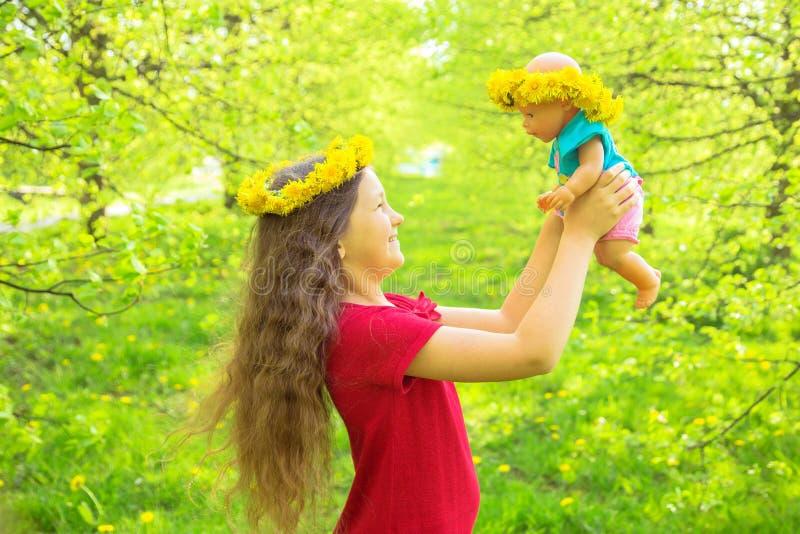 Den lilla ungen spelar med en docka lycklig din feriesommar för familj arkivbild