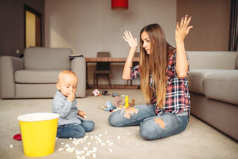 Den lilla ungen spillde popcorn, moderskapproblem arkivbild