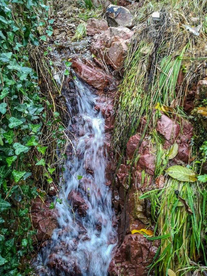 Den lilla vattenfallet med rödaktigt vaggar arkivbild