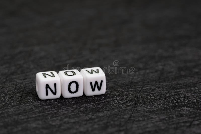 Den lilla vita kuben med alfabet som NU bygger ordet på mörk svart bakgrund med kopieringsutrymme genom att använda som angelägen arkivfoton