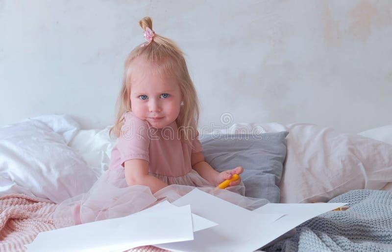 Den lite charmiga blonda flickan i rosa färger klär rymma filt-pennor och sitta på säng bland papper fotografering för bildbyråer