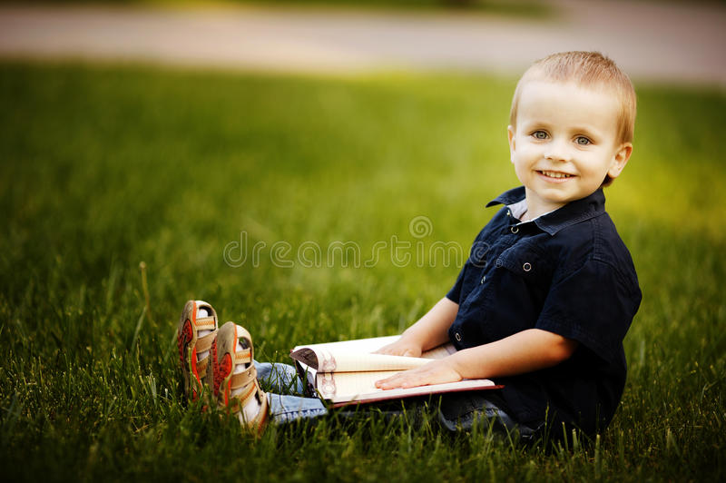 Den lite lyckliga pojken med bokar fotografering för bildbyråer