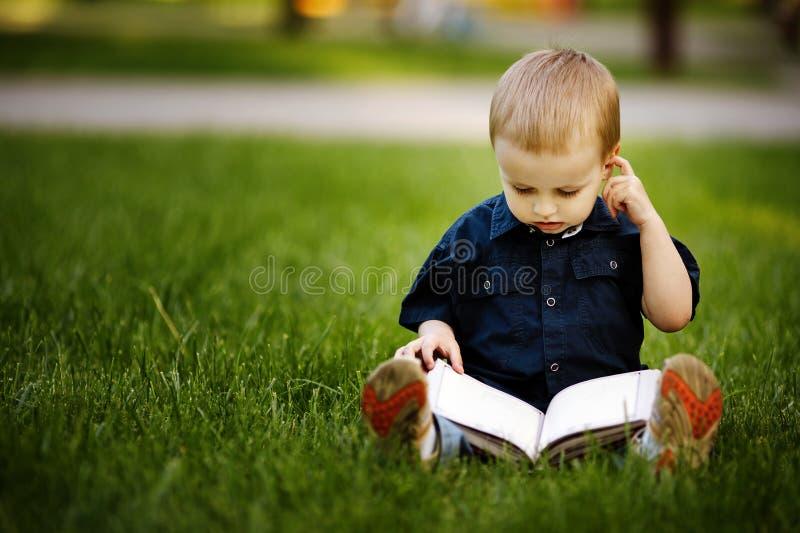 Den lite lyckliga pojken med bokar royaltyfria bilder
