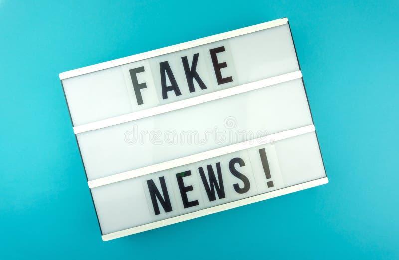 Den ljusa asken med rubriken fejkar nyheterna med mot blå bakgrund, bloggbegrepp arkivbild