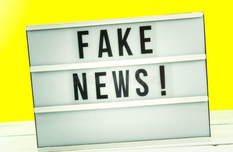 Den ljusa asken med rubriken fejkar nyheterna med mot gul bakgrund arkivfoton