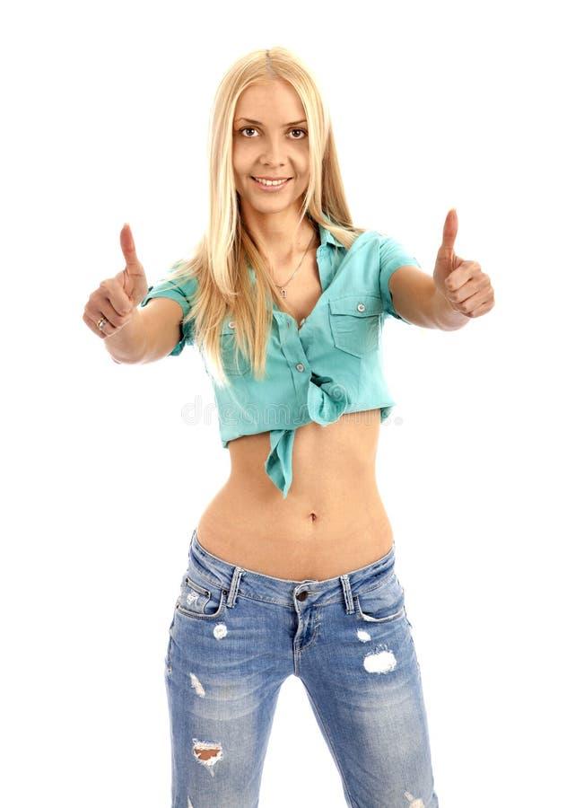 Den ljusa bilden av den älskvärda flickan med tummar up och ler arkivfoton