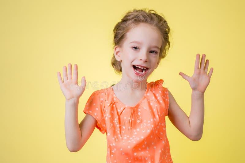 Den ljusa bilden av den lyckliga tonårs- flickan som visar henne, gömma i handflatan royaltyfri fotografi