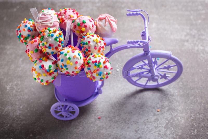 Den ljusa färgrika kakan poppar i dekorativ cykel på grå färger kritiserar fotografering för bildbyråer