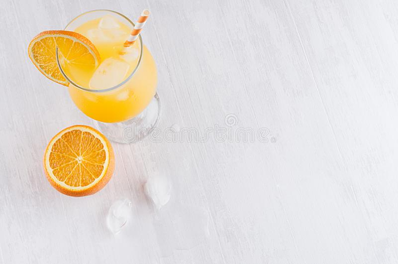 Den ljusa kalla tropiska orange coctailen av mogna apelsiner med sugrör, iskuber i elegans misted vinglaset på vit bakgrund arkivfoton