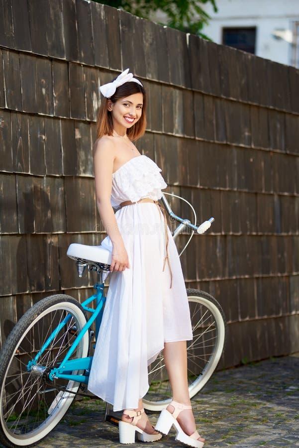 Den ljusa kvinnlign lutar på den retro cykeln mot den mörka väggen fotografering för bildbyråer