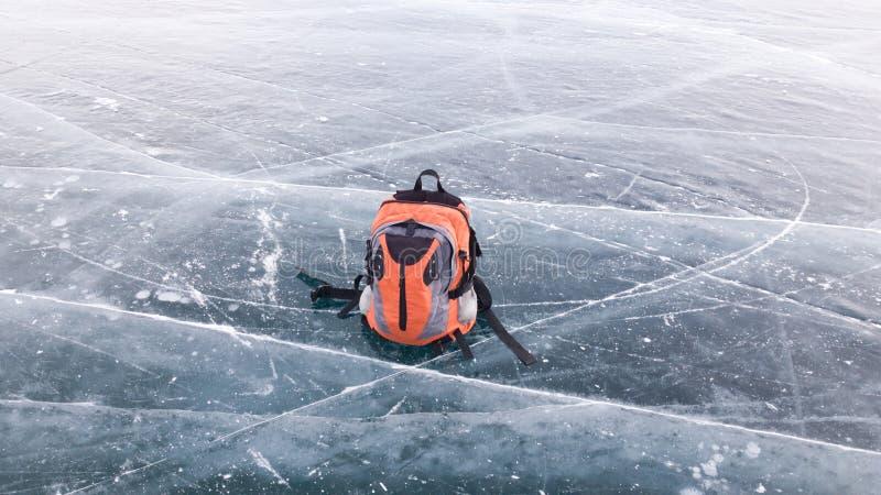 Den ljusa lilla fotvandra ryggsäcken ligger på isen av det djupfrysta Laket Baikal i Sibirien Resa-vandringen i den frostiga Ryss arkivbild