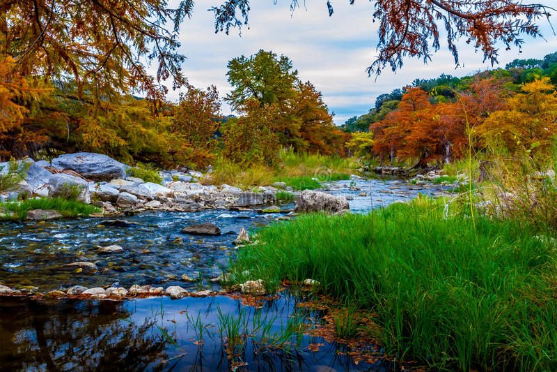 Den ljusa nedgången färgar omge en härlig kulllandsflod. royaltyfri bild