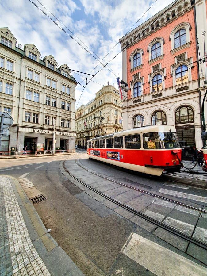 Den ljusa r?da sp?rvagnen i Prague b?r kunder runt om staden p? en ljus solig dag i April arkivbilder
