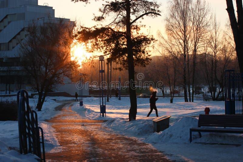 Den ljusa solen kikar ut bakifrån byggnaden i vinter snö är på spåret, och folket rusar för att arbeta och på affär royaltyfri fotografi