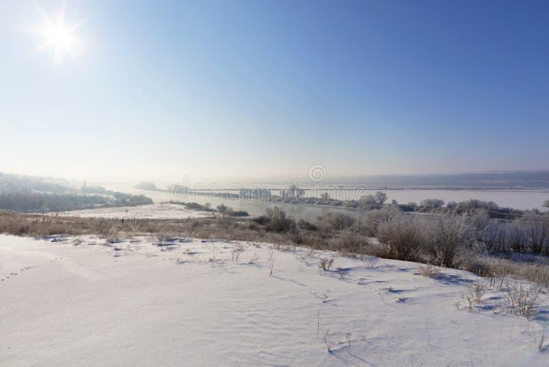 Den ljusa solen med en ogenomskinlighet i den blåa himlen exponerar floden och detäckte fälten i den frostiga morgonen royaltyfri fotografi