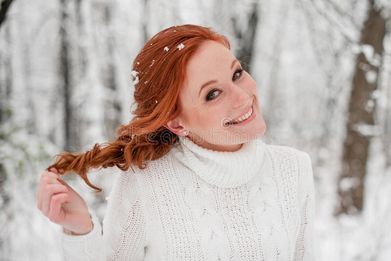 Den ljust rödbrun nätta flickan i den vita tröjan i vinterskogsnö december parkerar in Stående Gullig tid för jul royaltyfri bild