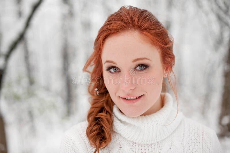 Den ljust rödbrun trevliga flickan i den vita tröjan i vinterskogsnö december parkerar in Stående Gullig tid för jul arkivbilder