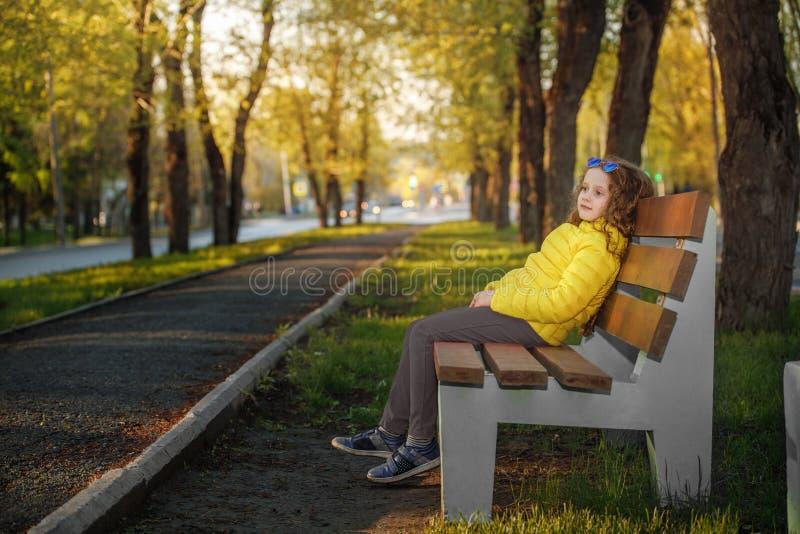 Den Llittle flickan som vilar i en höst, parkerar royaltyfri bild