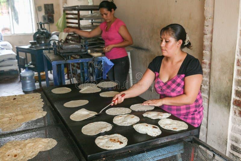 Den lokala kvinnan gör hemmet gjorde tortillor från havredeg i ett smal royaltyfri bild