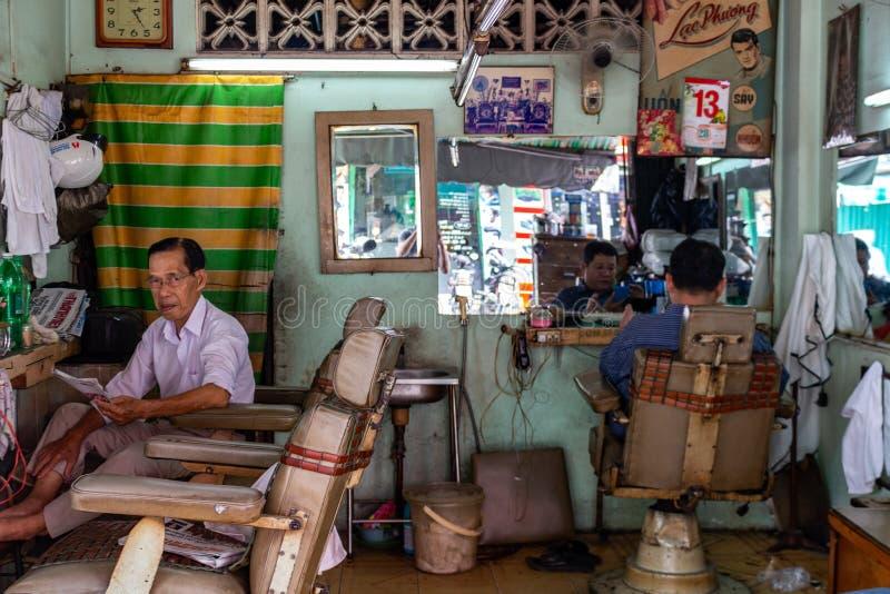 Den lokala tappningbarberaren shoppar Saigon Vietnam arkivfoto