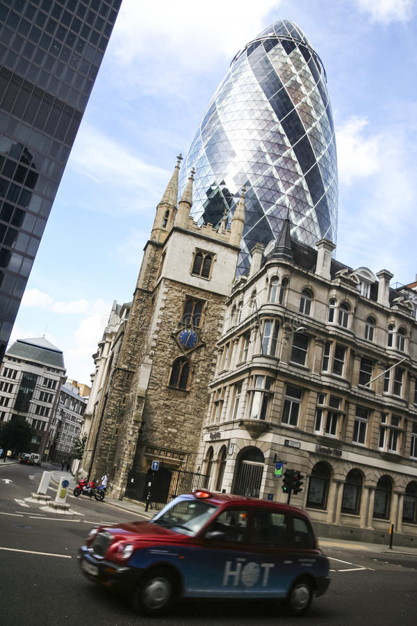 Den London staden taxar caben som kör past ättiksgurkabyggnad arkivbild