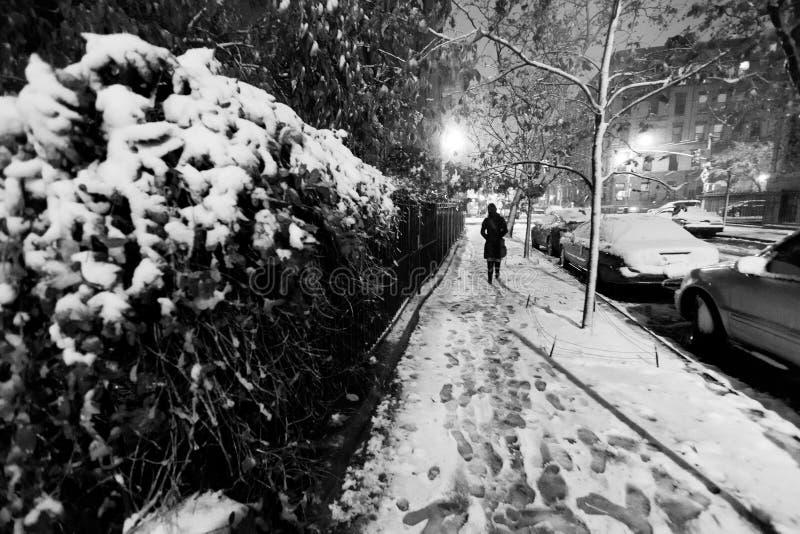 Den Lone kvinnan som går på snowen, täckte trottoar av en Harlem stre arkivfoton