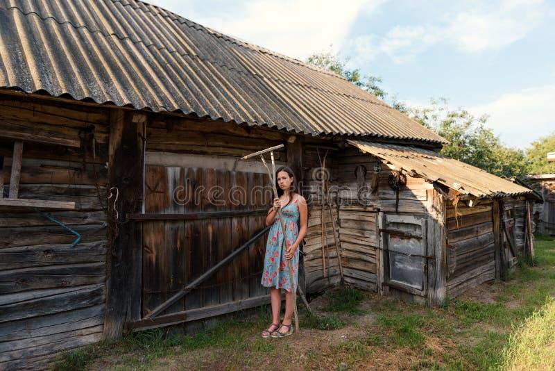 Den LookBook ståenden av en flicka i en lantlig tappningklänning med krattar nära en lantlig ladugård och ladugård i en borggård arkivfoton
