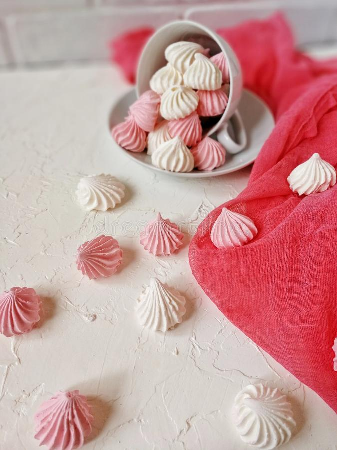 den luftiga marängviten och rosa färgen hälls från ett vitt porslintepar på en ljus tabell med en rosa löpare arkivfoton