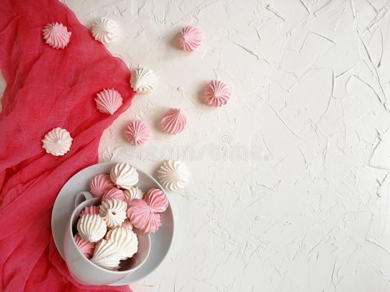 den luftiga marängviten och rosa färgen hälls från ett vitt porslintepar på en ljus tabell med en rosa löpare arkivbilder