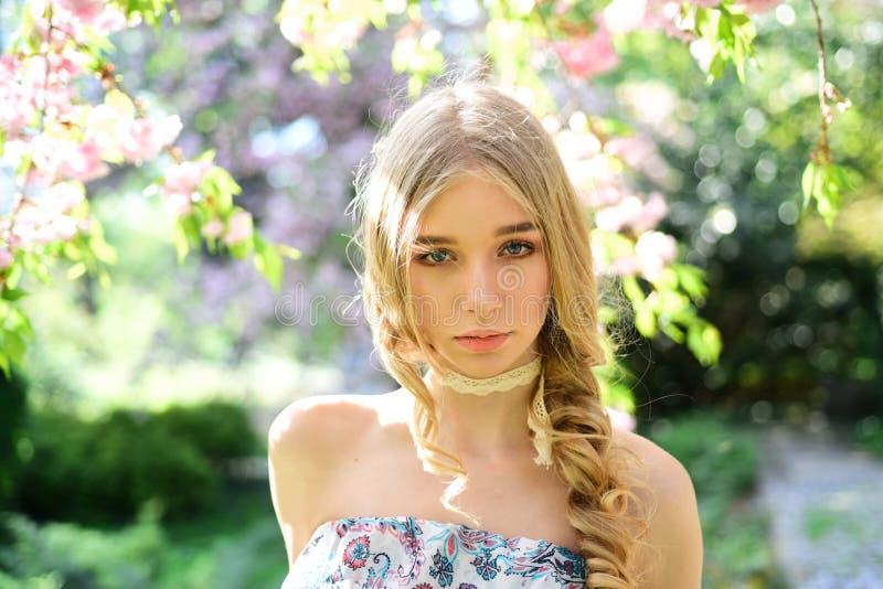 Den lugna blonda flickan som tycker om vårdag i blom- trädgård, fyllde med ny arom av blommablomningen Nätt ung dam med royaltyfri fotografi
