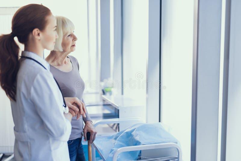 Den lugna mogna damen ser doktorn i sjukhuset royaltyfri bild