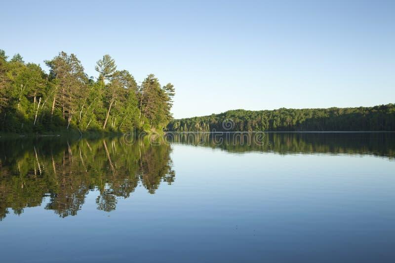 Den lugna nordliga Minnesota sjön med sörjer träd på solnedgången på en clea royaltyfria foton
