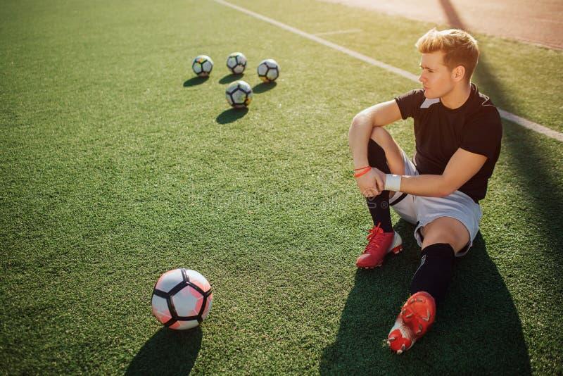 Den lugna och fridsamma spelaren som sitter på gräsmatta, vilar honom ser till vänstersida Foour bollar är bakom, och en är främs royaltyfri foto