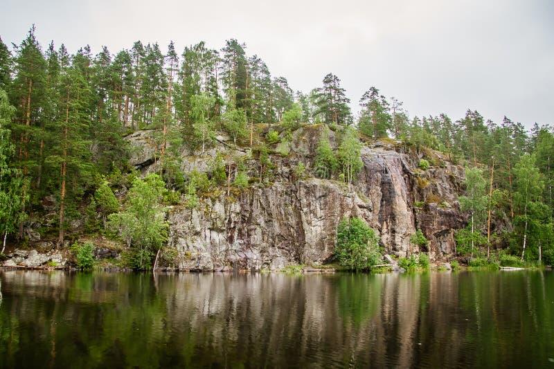 Den lugna sjön med reflexion av vaggar på kusten arkivfoton