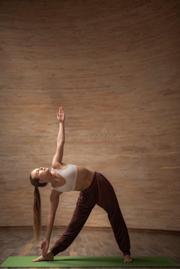Den lugna unga damen som öva den kretsade triangeln, poserar på yogagrupp arkivbild