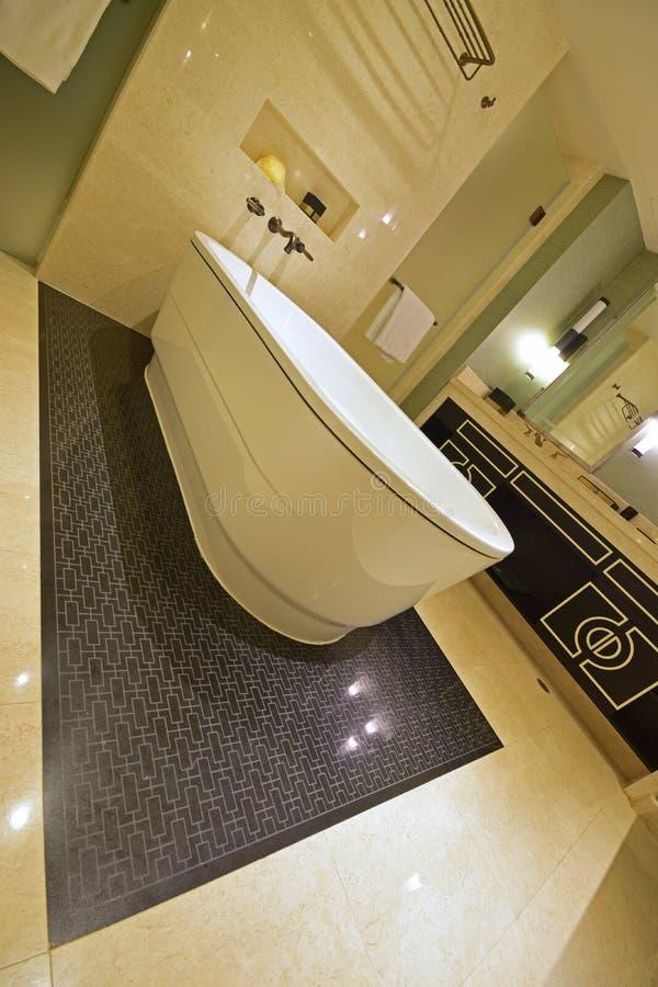 Den lutade sikten av det klassiska designbadrummet med badkaret, marmorväggen och versace inspirerade den kabineda dörren arkivbilder