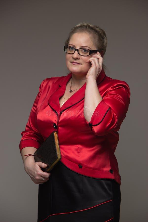 Den lyckade affärskvinnan är inte ung i en dräkt med en anteckningsbok arkivbild
